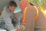 Nic Marchesi helps Steven Smith as they put his clothes into a washing machine