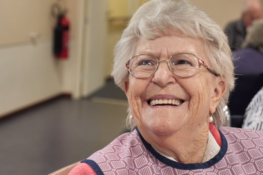 An elderly woman in spectacles smiles broadly