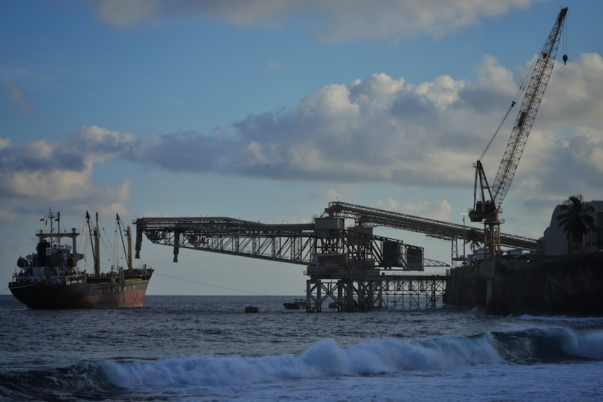A boat on the water next to a mining operation.