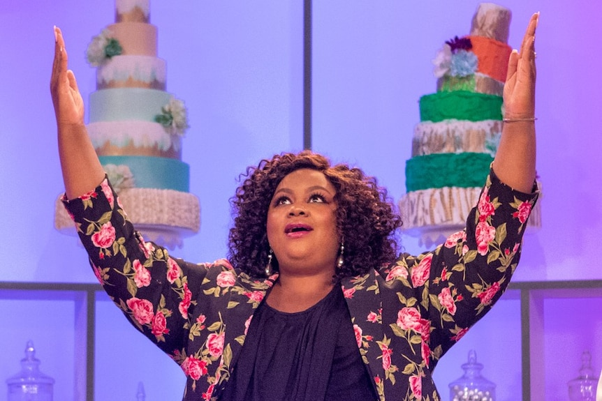 A Black woman in her 30s with curly hair and floral jacket raises her arms to the sky and looks up in wonder