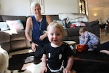 Alyssa Foster laughing in her loungeroom with her three children.