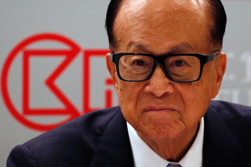 A man in thick black rimmed glasses and a suit looking serious