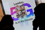 Pedestrians walk past an advertisement promoting the 5G data network at a mobile phone store in London.