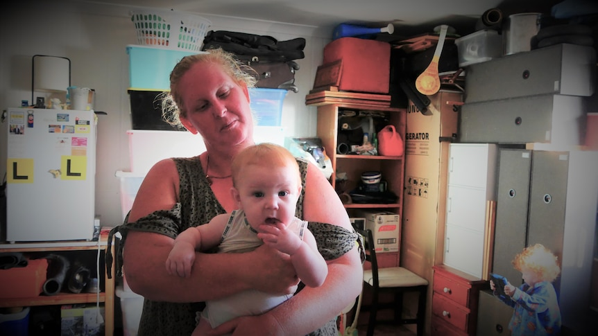woman holding a baby with kitchen behind