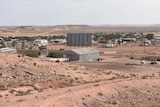 A few houses and buildings surrounded by red dirt in an outback landscape