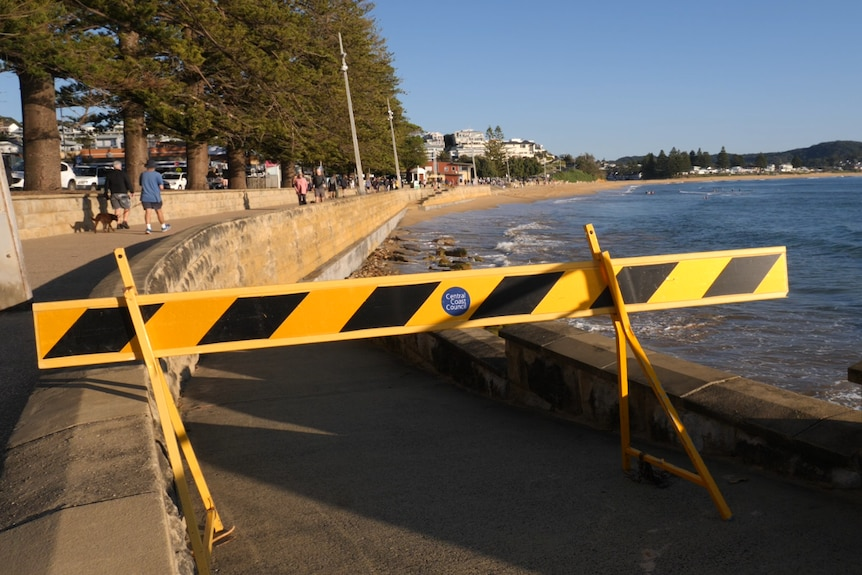 A yellow sign blocking access to a broken ramp that leads to the sand