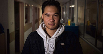A mid-shot of Terry Vo standing in the corridor of Princess Margaret Hospital posing for a photo wearing a hoodie and jacket.