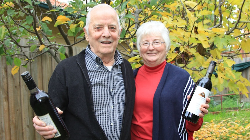 A man and woman stand in their garden, each holding a bottle of red wine.