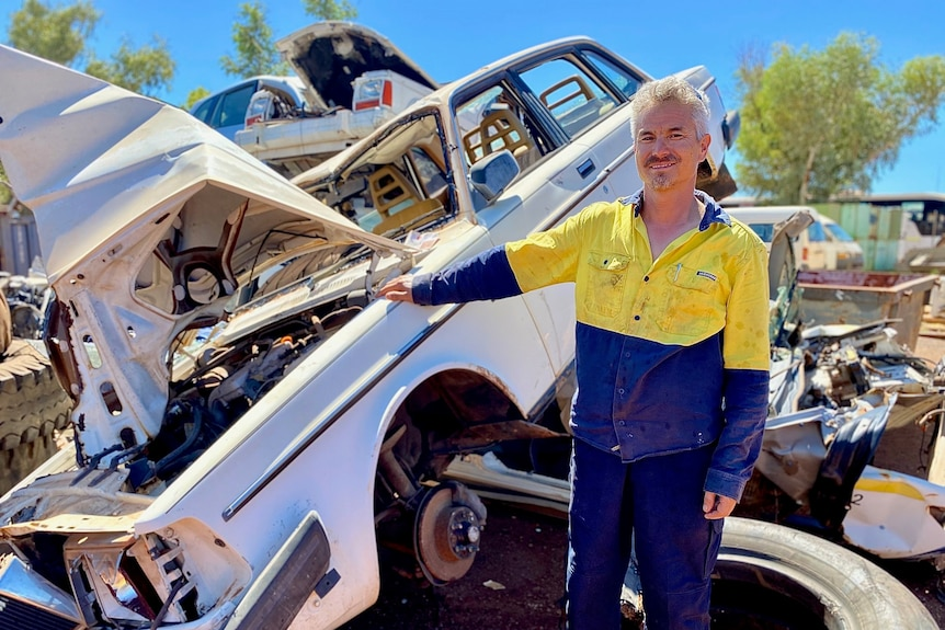A man in high vis work clothes stands next to a white car wreck