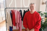 Carla Woidt smiling as she stands in front of a rack of clothing.