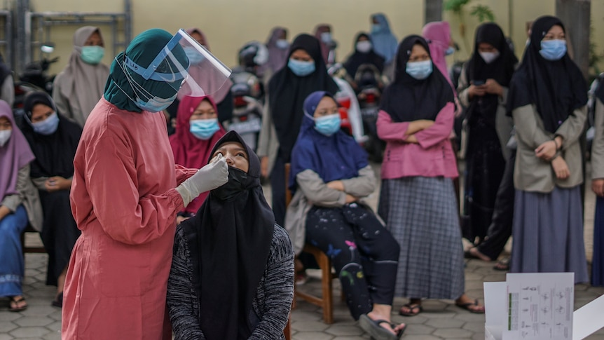 A medical worker collects a swab sample as other young women wait to be tested