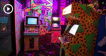 A very brightly coloured and patterned room, with three 80s-style video game machines.