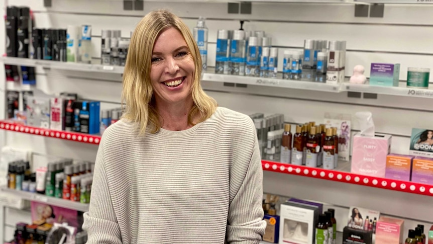 A woman smiles at the camera leaning on a shop counter