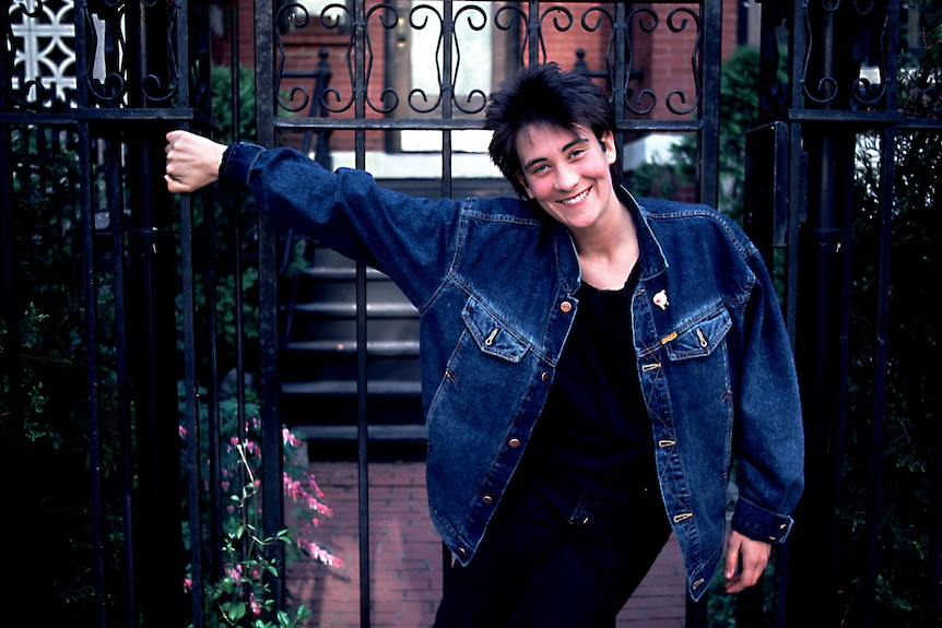 A young kd lang wearing a denim jacket, stands outside with one hand on a wrought iron fence.