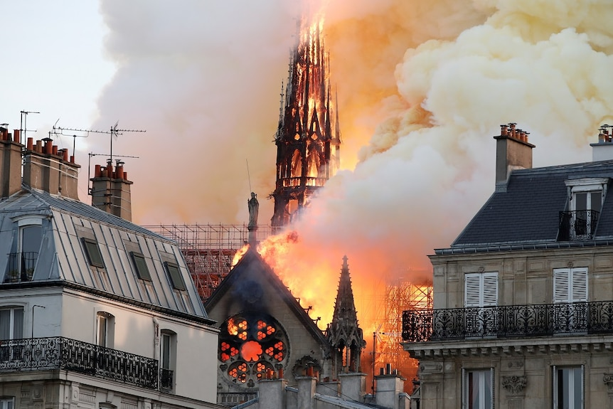 The roof and spire of a gothic cathedral are burned by bright orange flames while thick smoke fills the sky