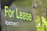 "A black sign with green letters reading ""For Lease, Apartment 1""."