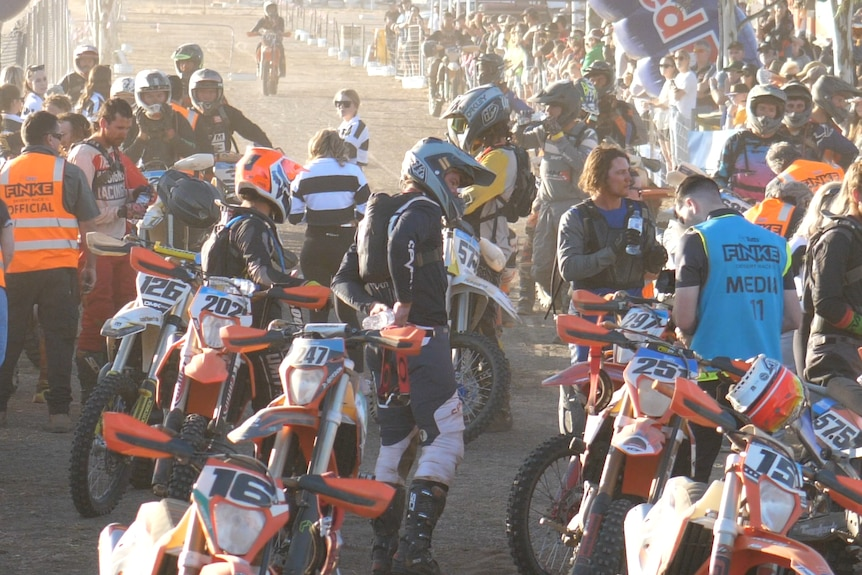 A crowd of dirt bike riders in protective gear gathered on a road in the outback.