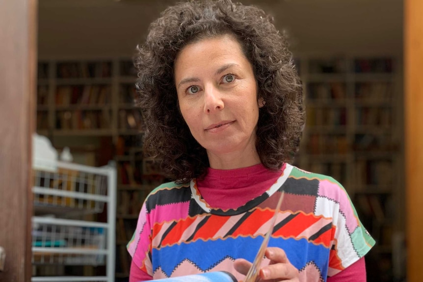 a woman in a multi-coloured shirt opens the pages of a book while looking at the camera