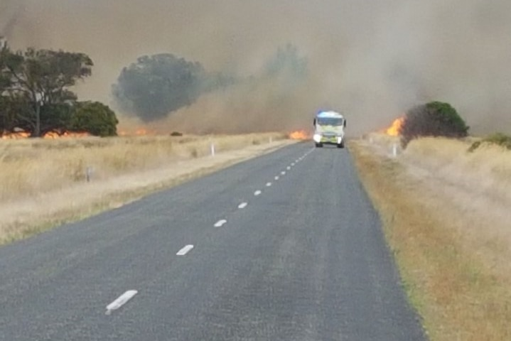 A CFS truck driving along the road with a fire burning behind