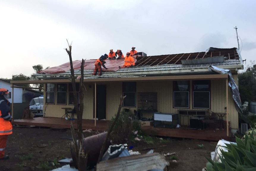Emergency workers on a damaged roof.