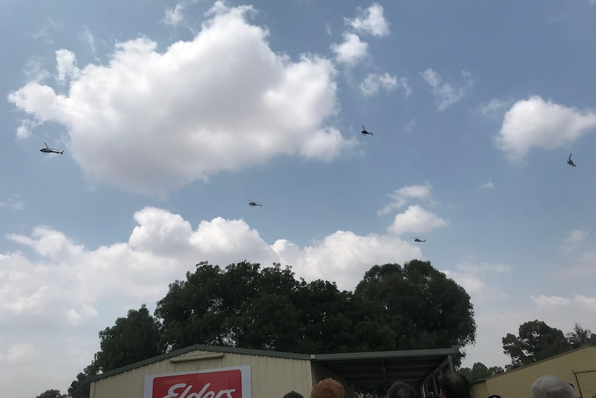 Five helicopters fly over a group of people and buildings.