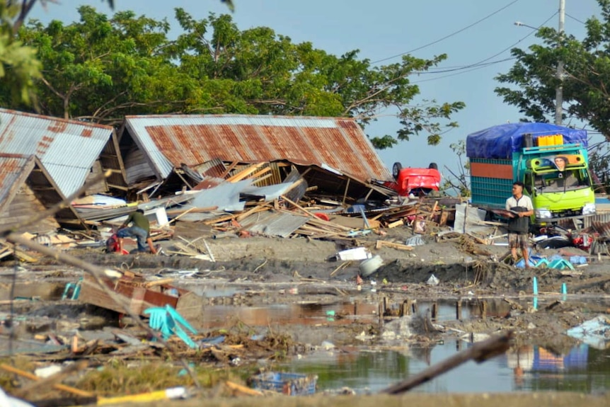 A man stands amid water and debris caused by a tsunami in Palu