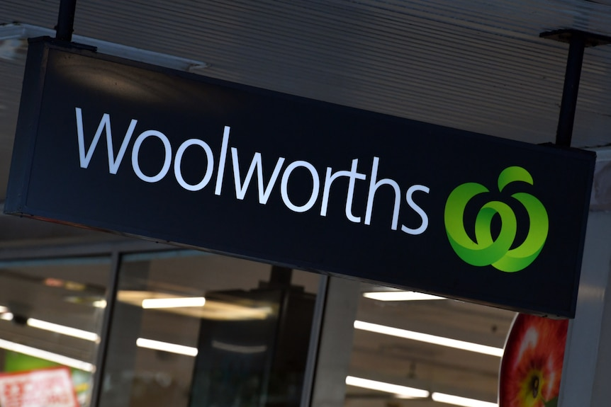 A woolworths sign, light up over the entrance to the supermarket.