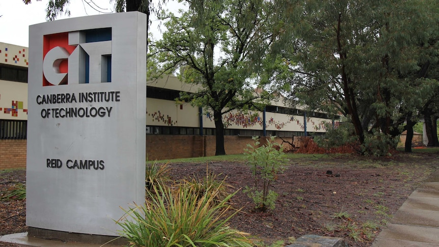 A sign reading Canberra Institute of Technology sits in front of a dark brown building.
