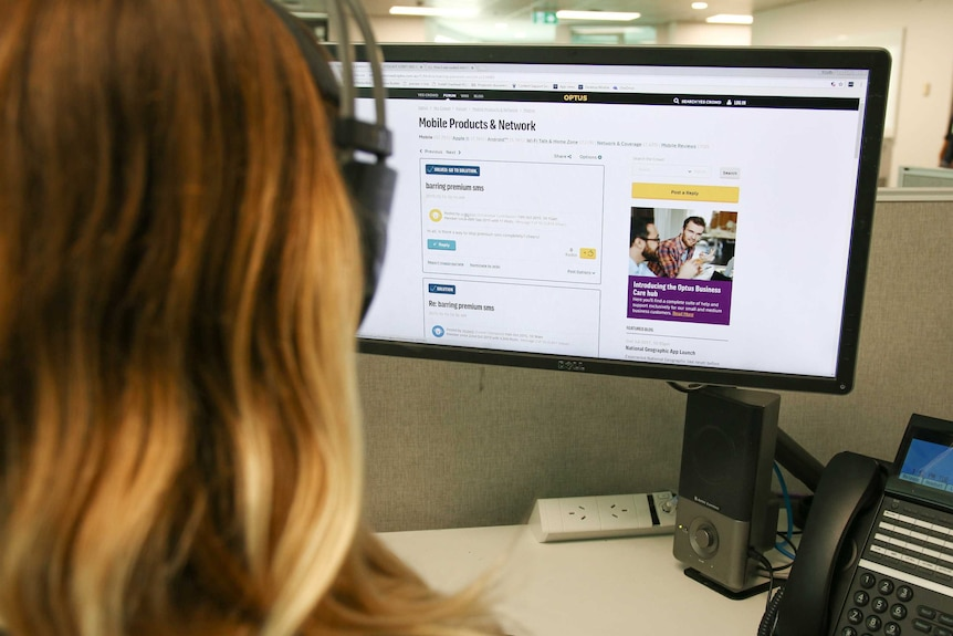 Woman sits in an office with headphones on looking at an Optus webpage