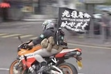 """A man riding a motorbike with a flag which reads: """"Liberate Hong Kong""""."""