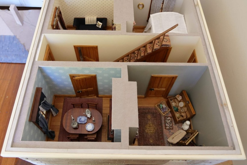 Photograph of a dolls house from above with no roof, four rooms and stairs