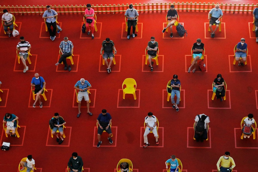 People watch an outdoor movie screening while socially distanced in Singapore