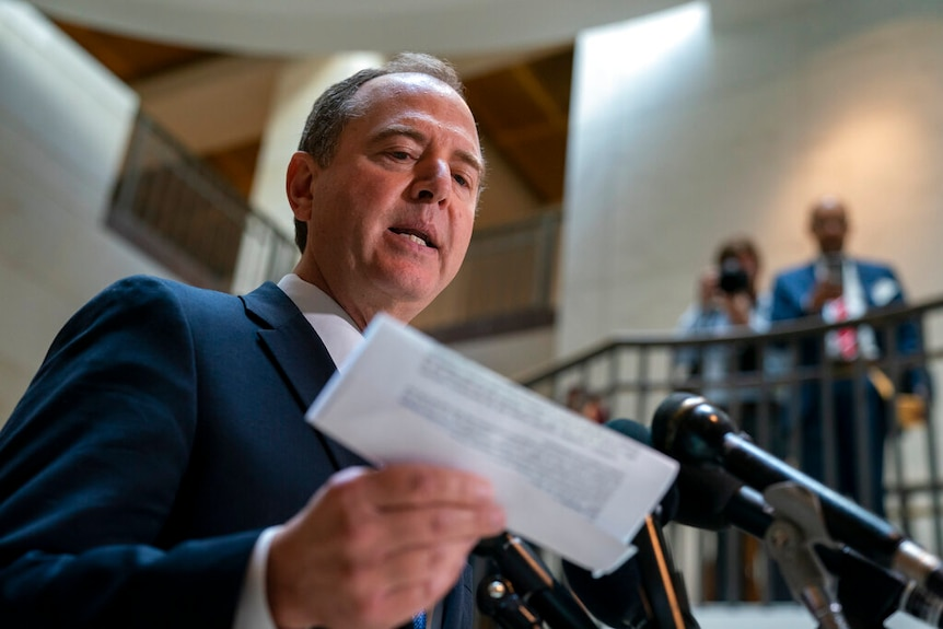 You look up at Adam Schiff as he speaks in front of a cluster of microphones while holding a folded white printed document.