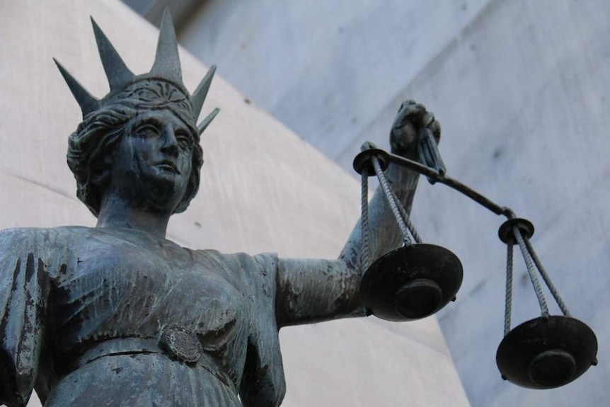 Lady Justice holds her scales outside a court building.