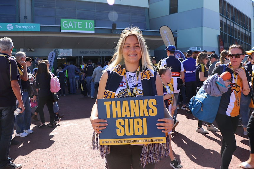 "Annelise Hill, dressed in West Coast Eagle stiped scarf and AFL jersey, holds a sign saying ""Thanks Subi""."