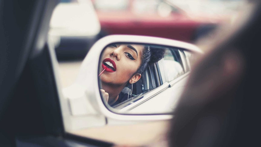 Woman applying lipstick in the side mirror of her car for a story about how a woman's appearance affects her career