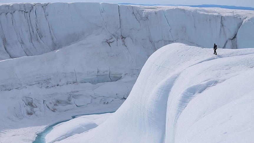 A person walks on a massive white ice sheet