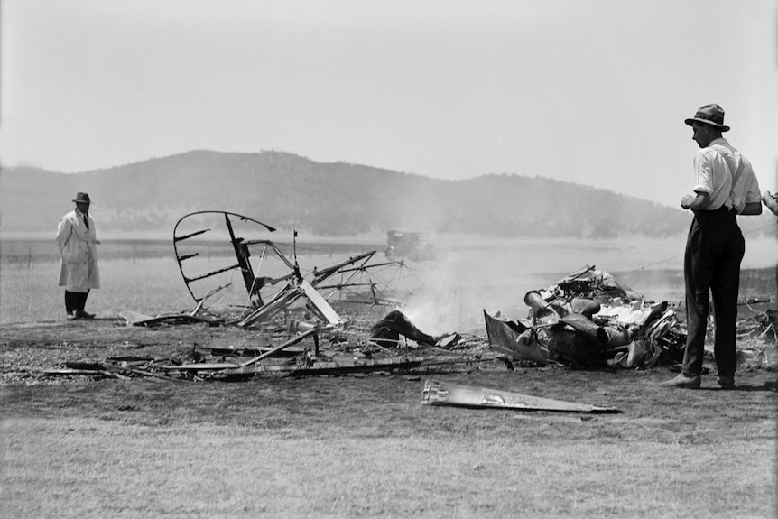 Black and white photo of a plane crash. The plane has been reduced to rubble, which is still smoking, in a field.