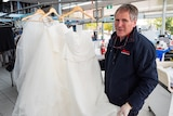 John Colgan displaying bridal dresses inside dry-cleaning store.