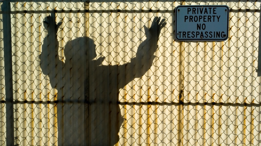 Man reaches for the top of a translucent fiberglass  fence while a sign on the other side warns of not trespassing.