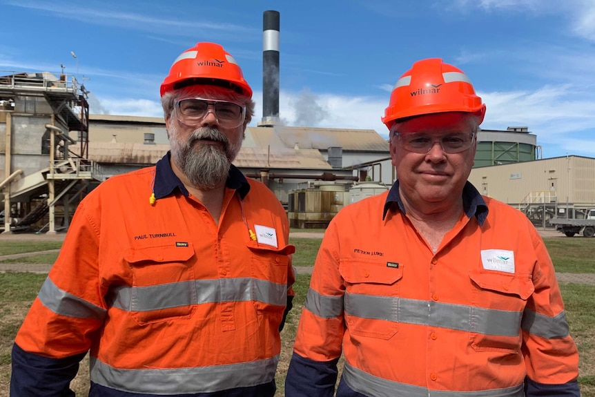two men in hi vis in front of a sugar mill