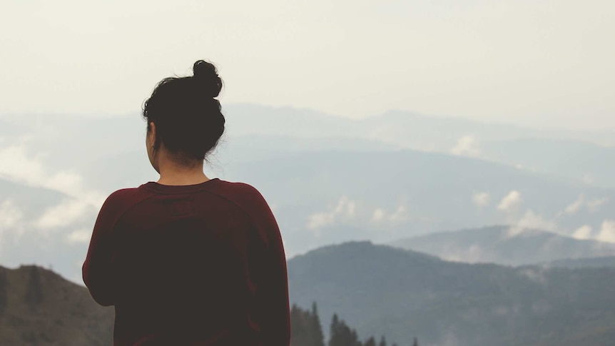 A woman stands alone in contemplation, looking out at snow capped mountains.