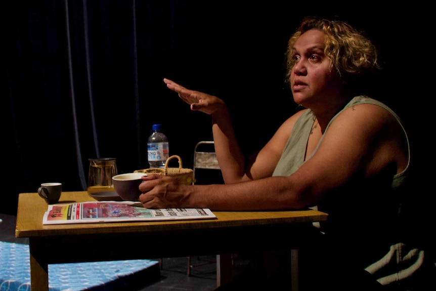 Indigenous woman sitting at desk with coffee cup making a point with her hand talking to left of photo