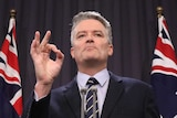 Mathias Cormann holds up his right hand in an 'OK' motion, while standing at a lectern in front of two Australian flags.