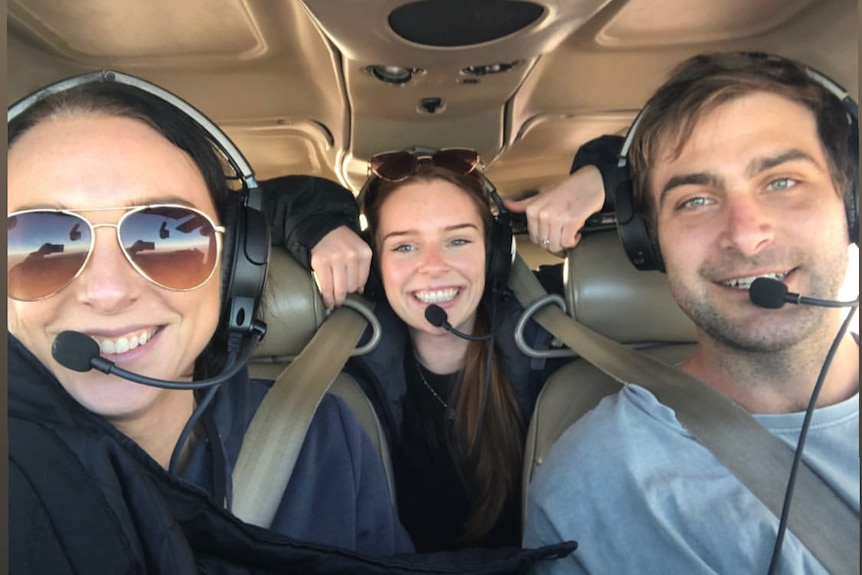 Three people inside a small plane