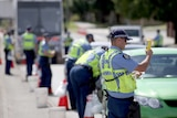 Police officers holding testing machines with a row of cars.