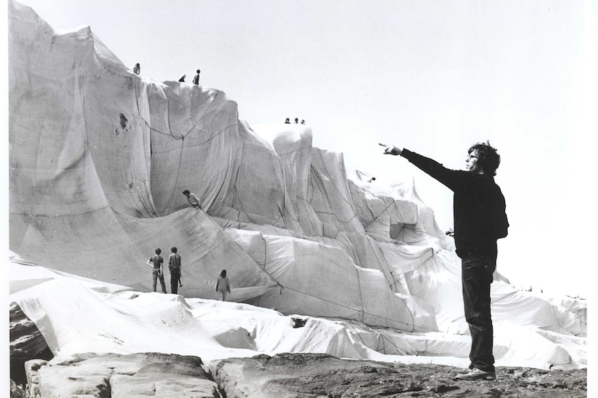 the artist Christo stands in front of wrapped coast pointing to something in the distance.