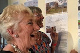 Women looking at a large pinboard covered in designs for public toilets