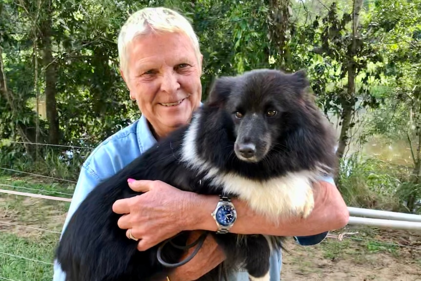 A woman with short hair holds a little black and white dog.
