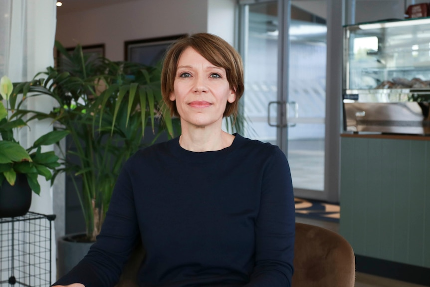 A woman wearing a navy jumper sitting in a chair in a showroom looking at the camera.